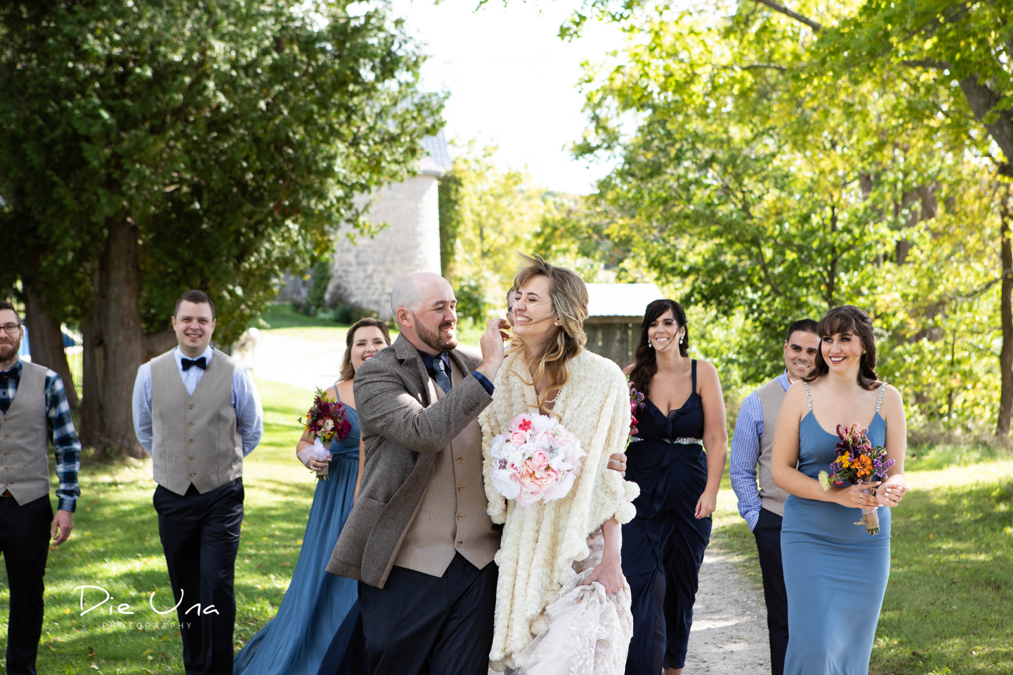 groom fixing brides hair on windy wedding day wedding party in the background walking.jpg