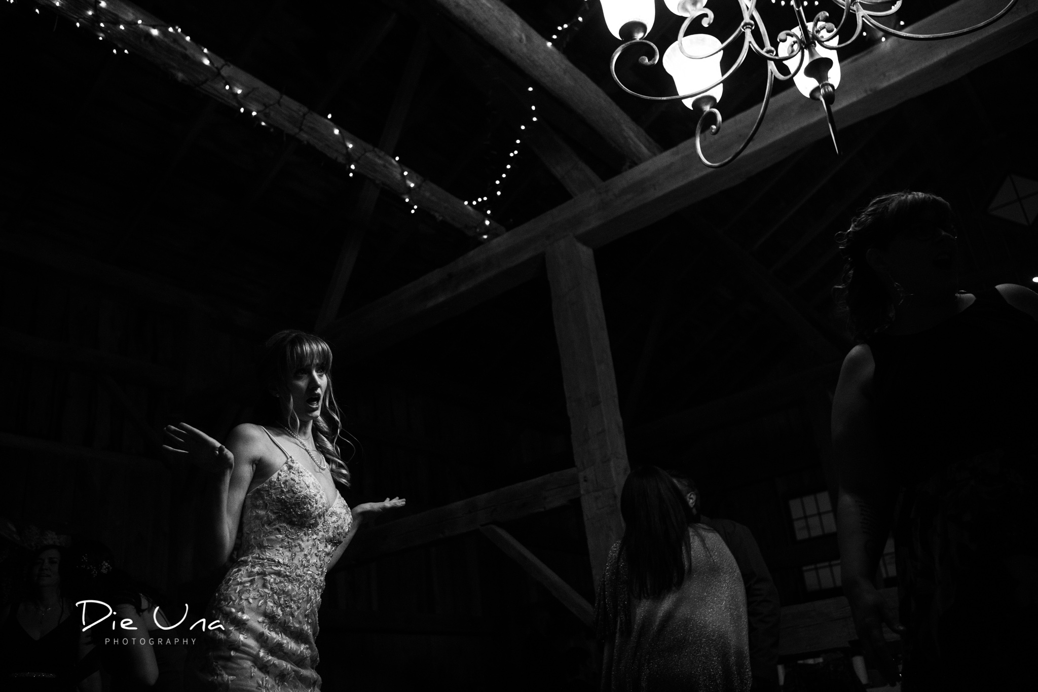 high contrast black and white photography bride dancing with chandelier in frame.jpg