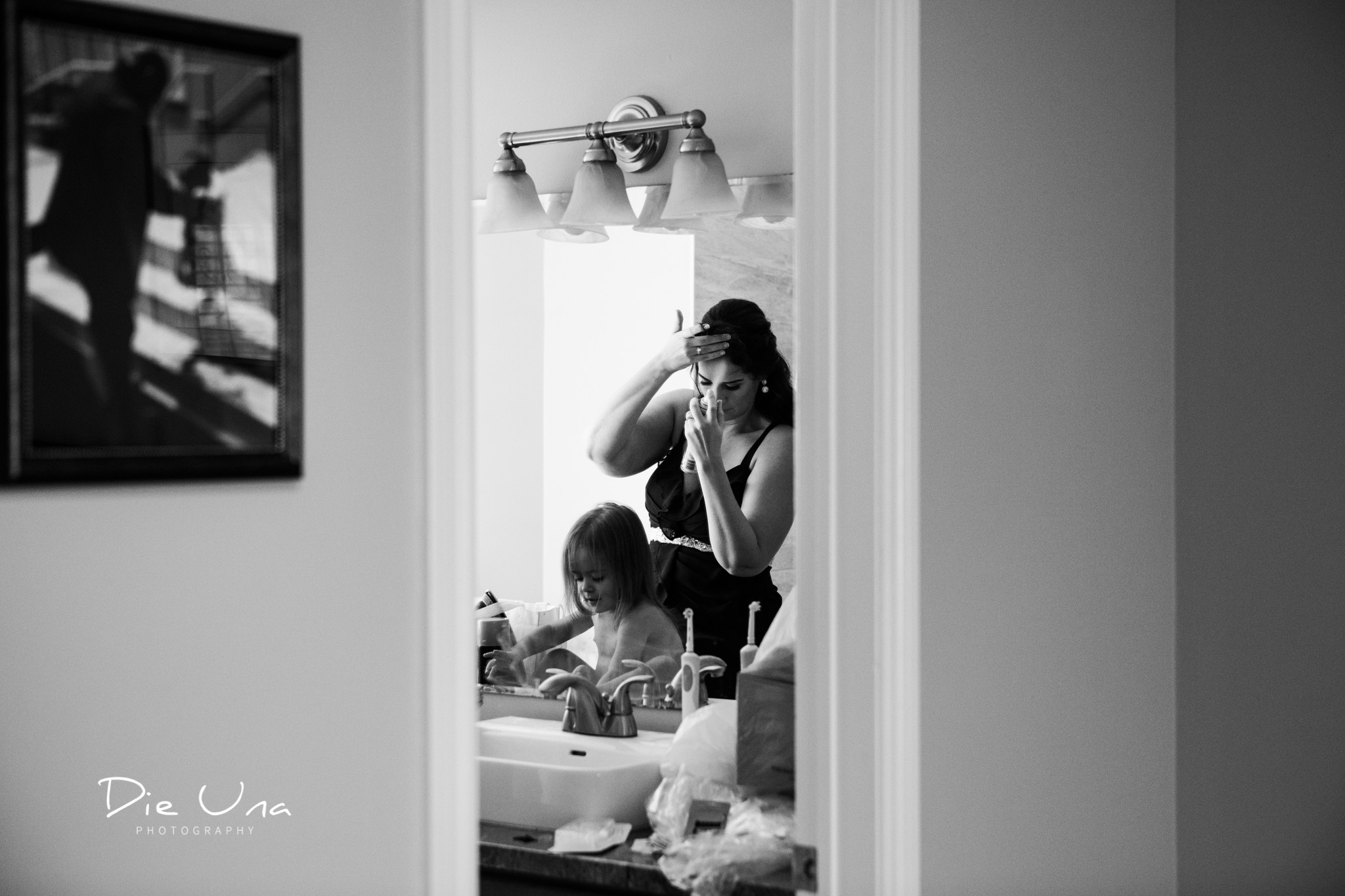 maid of honour putting on finishing touches for hair reflected in bathroom mirror with flower girl.jpg