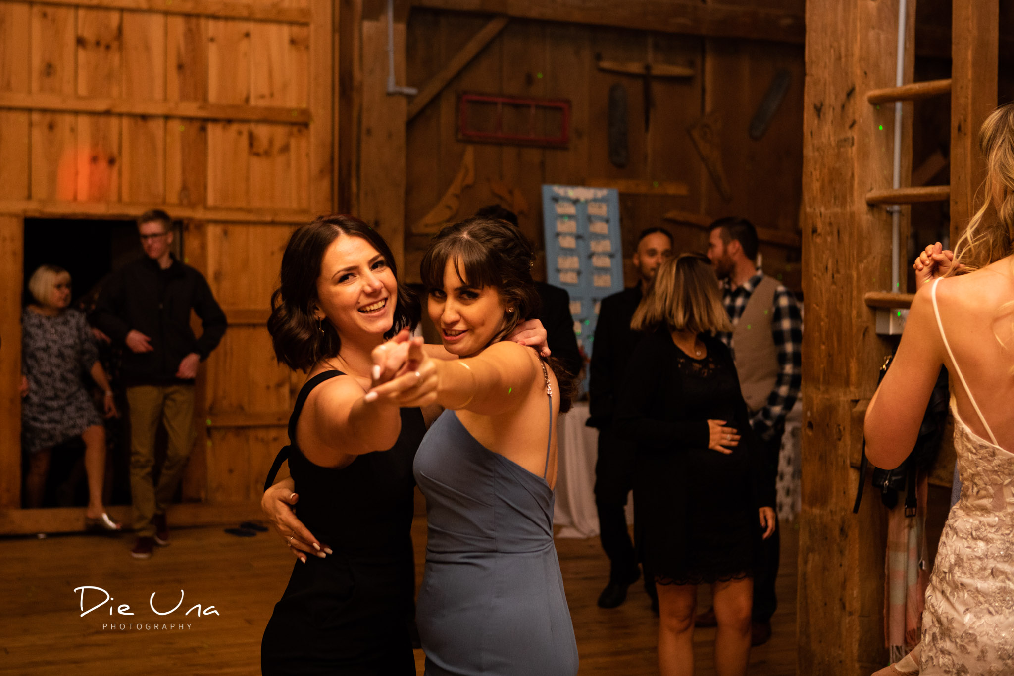 two female wedding guests dancing spiritedly during barn dance reception kitchener wedding photographer.jpg