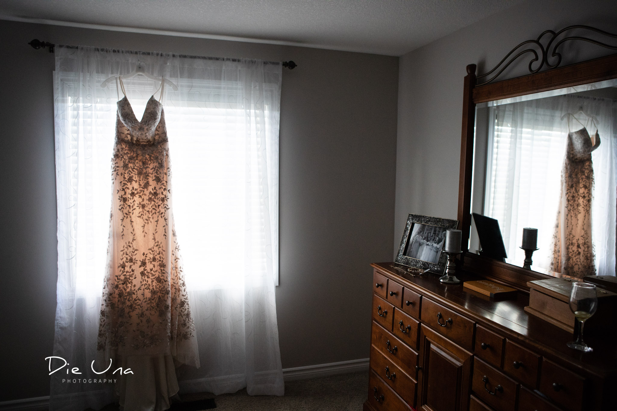 wedding dress hanging in window and reflected in dresser mirror.jpg