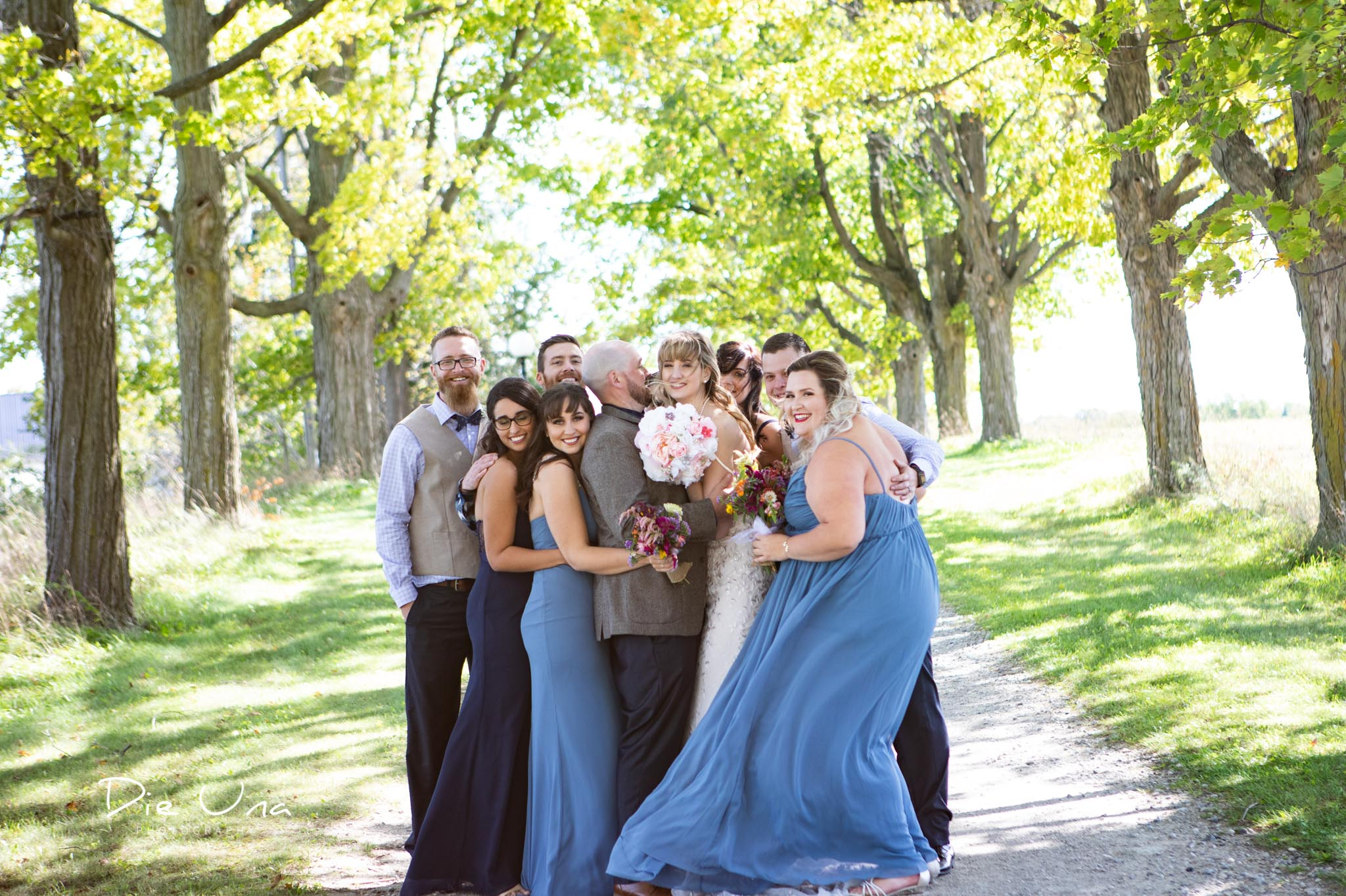 wedding party giving bride and groom a group hug on tree lined driveway.jpg