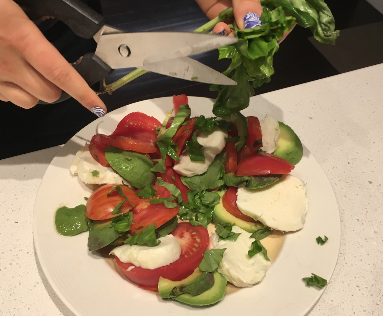 my daughter putting the finishing touches on a Caprese Salad