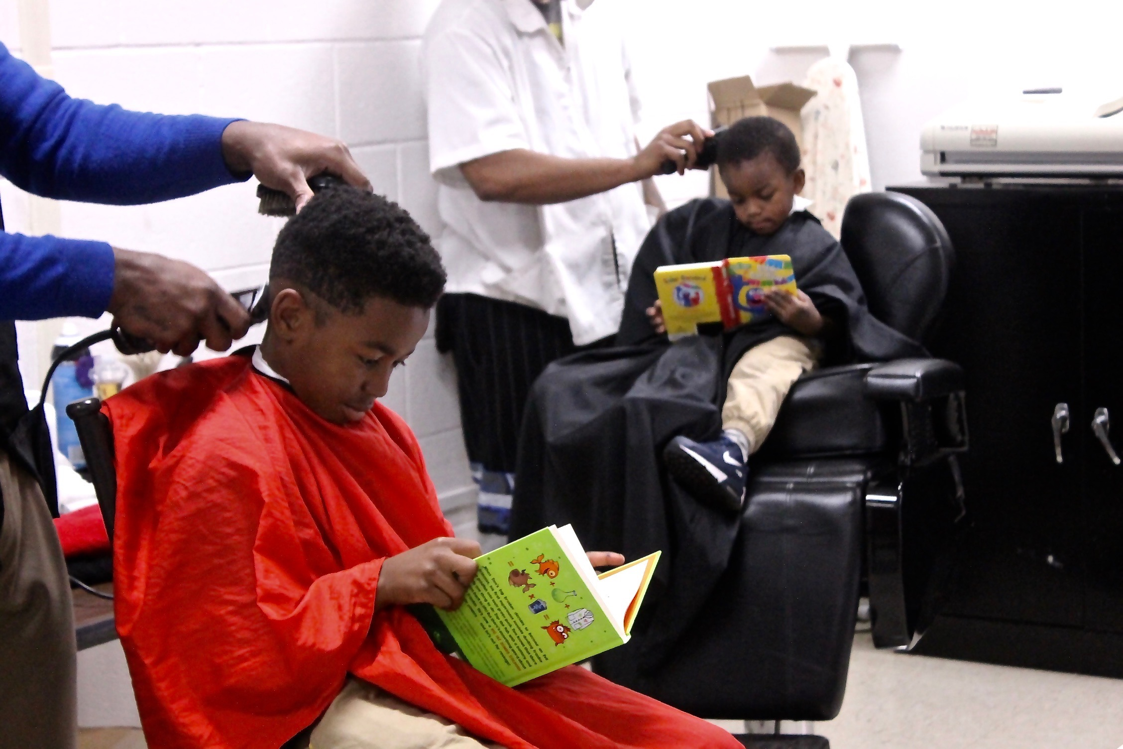 Two Kings Reading Their Books While Getting Their Haircuts at Support The Port Foundation, Inc. Come Through it's Lit Book Drive & Literature Initiative
