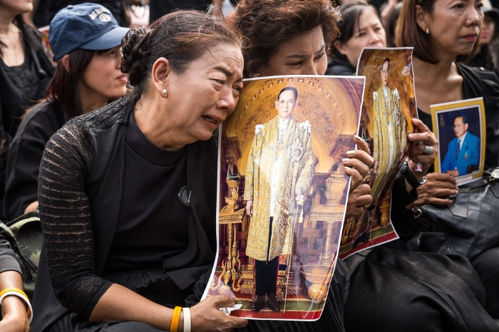 Mourner cries over a picture of King Bhumibol Adulyadej
