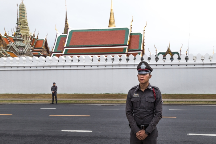 Policemen watch the crowd in front of the Royal Grand Palace in Bangkok