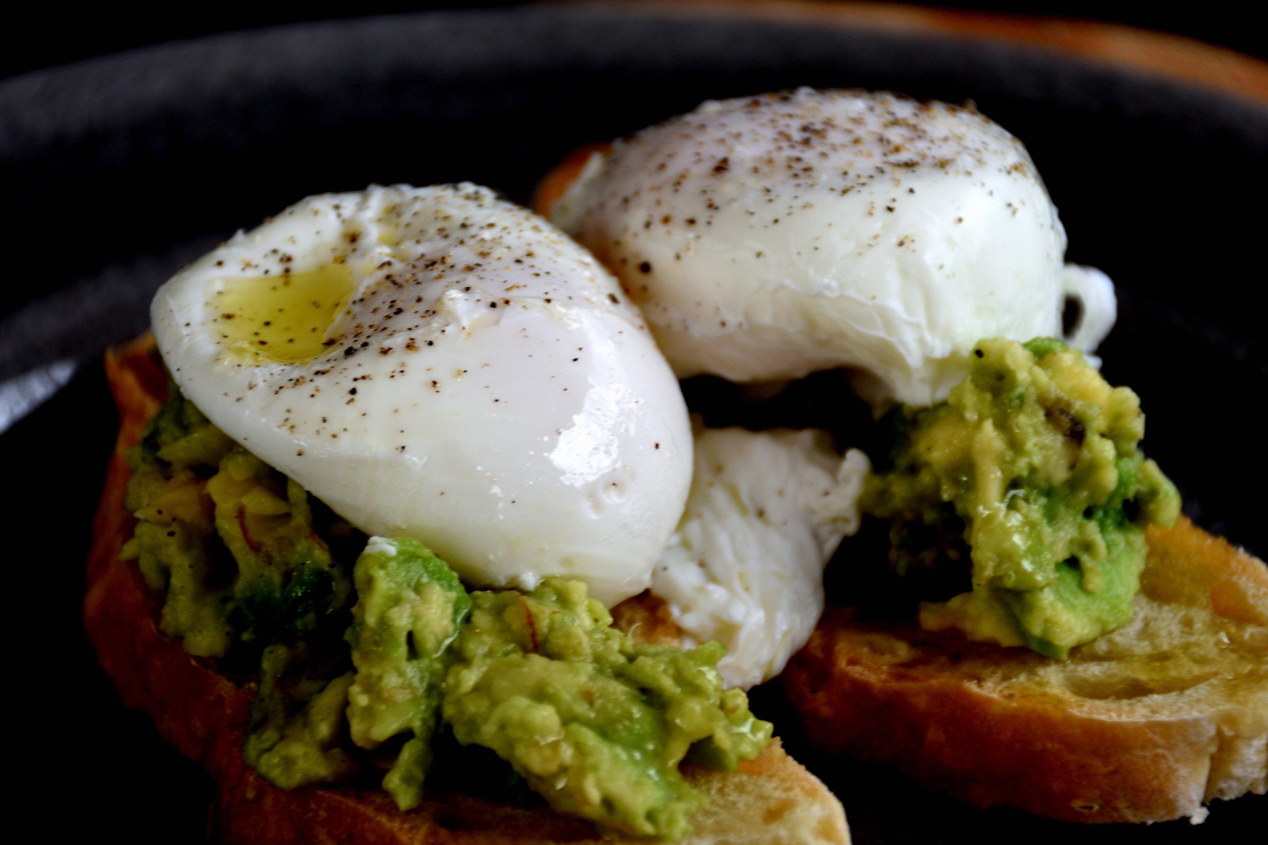Poached eggs on mashed avocado sandwish.