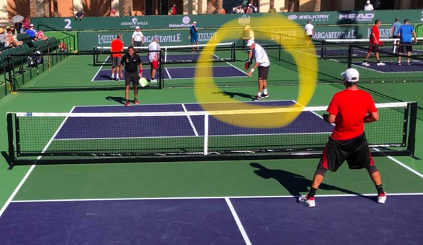 Standing out wide when serving makes it easier to get a rebound that pulls the opponent off the court.