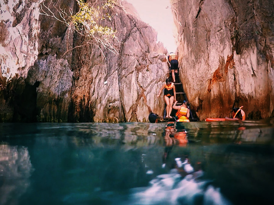 At Twin Lagoon, to cross from one lagoon into the other you can either climb a short ladder or swim under the limestone rocks. Alex was brave enough to go under.