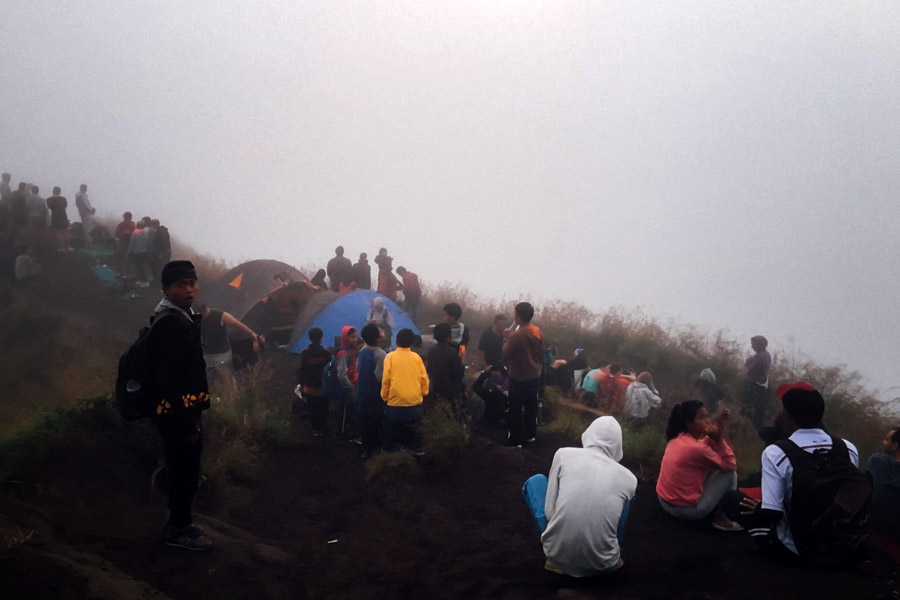 Campers and hikers gathered for a foggy sunrise atop Mount Batur.