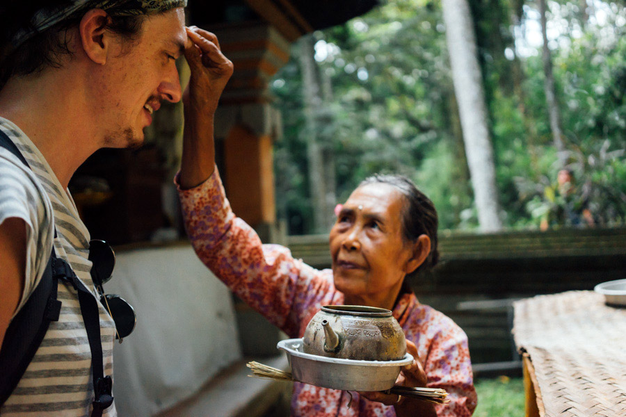 The lovely Balinese woman placing  bija  on Alex's forehead.