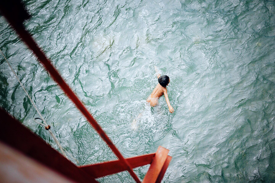 One of many children swimming upstream in the Bohorok River, seen from a makeshift suspension bridge.