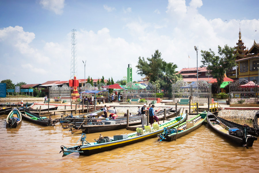 Boats carrying tourists, transporting goods, and selling produce crowd the landing at the main temple.