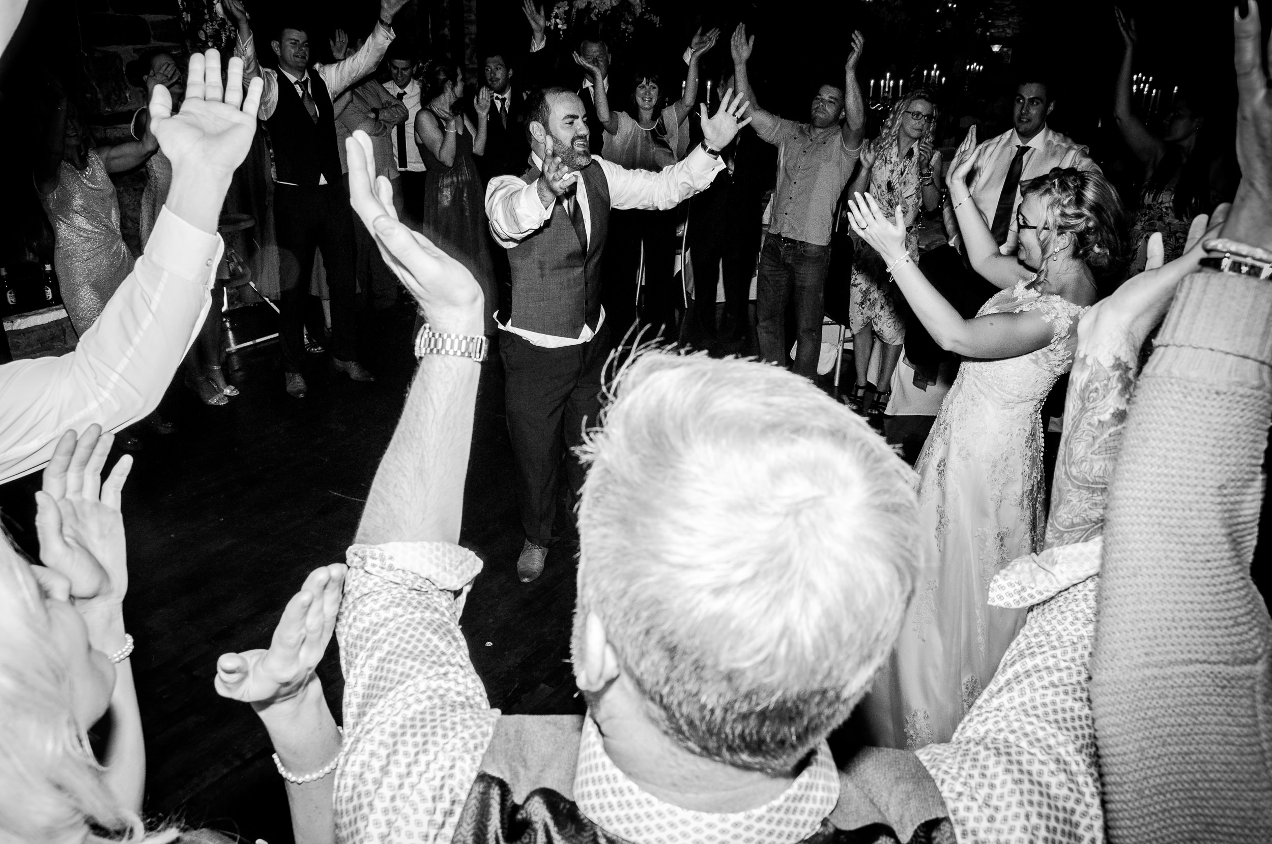 Black and White Wide Picture with Deep Fcous of Bride and Groom in the middle of the dancefloor with arms in the air encircled by their wedding guests at the end of the night. Cool as you like.