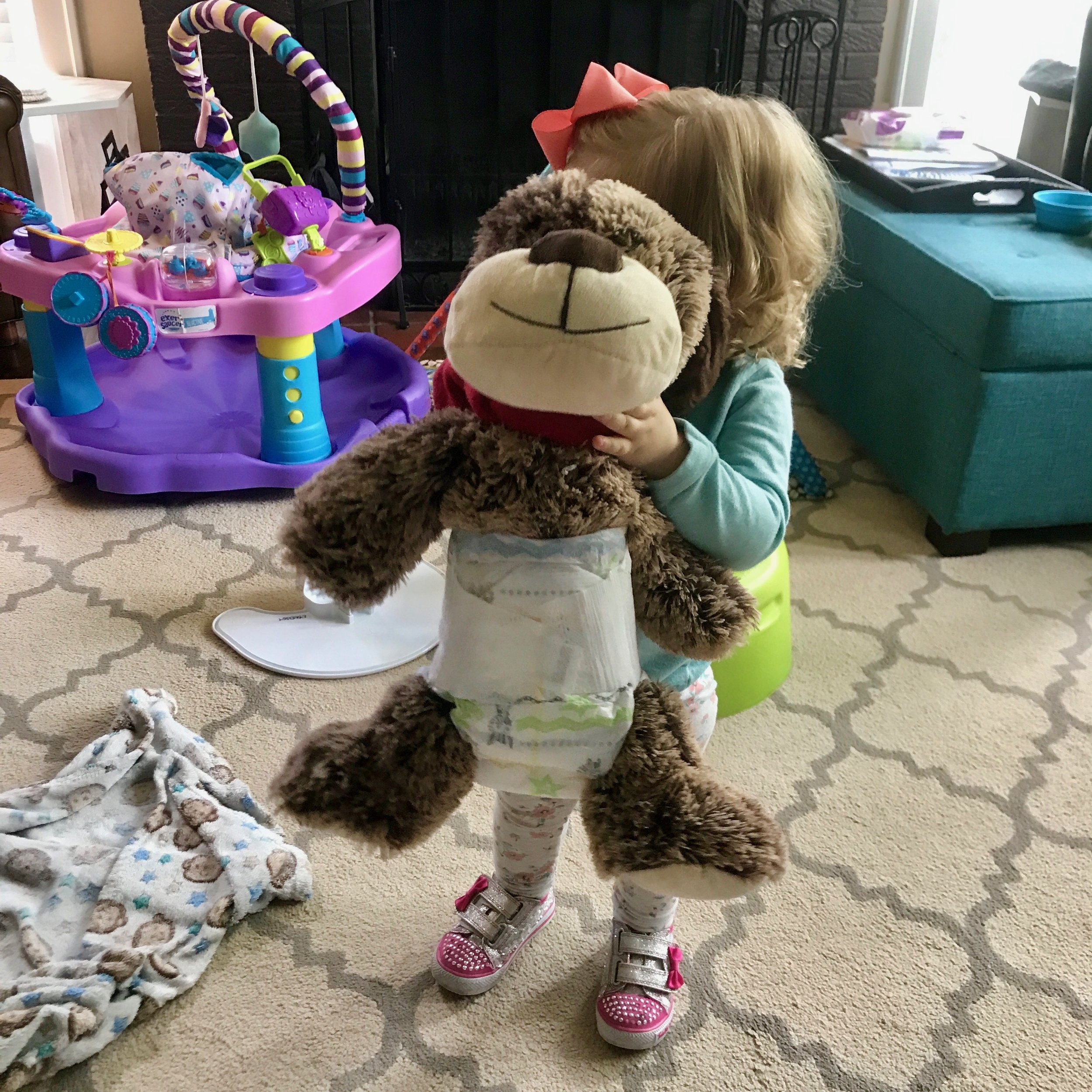 Little Mama loves putting diapers on all the stuffed animals.