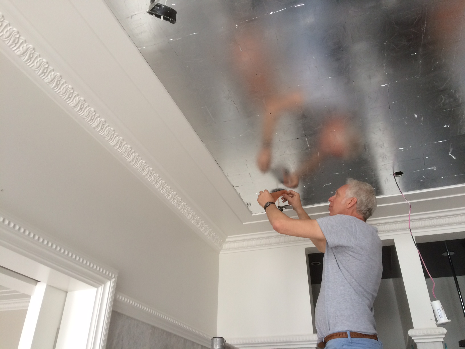 Silver leafing a ceiling in process .