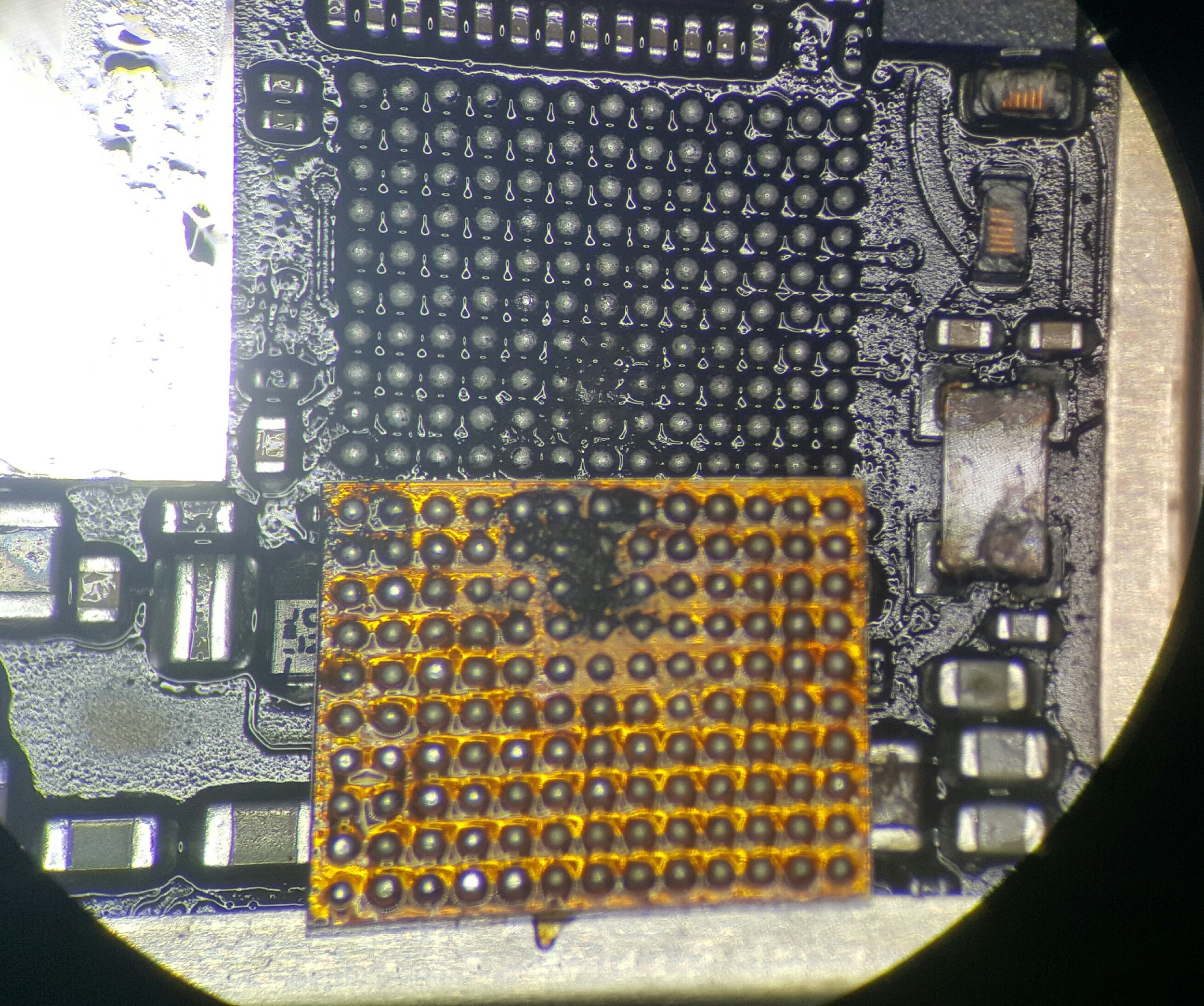 Shorted, burnt and corroded contacts beneath the Touchscreen IC on an iPhone 6 Plus