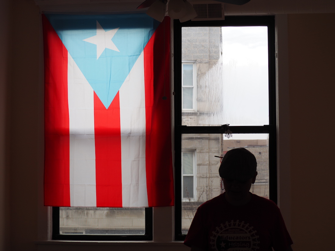 Angie stands in front of the window in their three-bedroom apartment in Chicago. She doesn't know when or if her family can return to Puerto Rico. (Sofi LaLonde/MEDILL)
