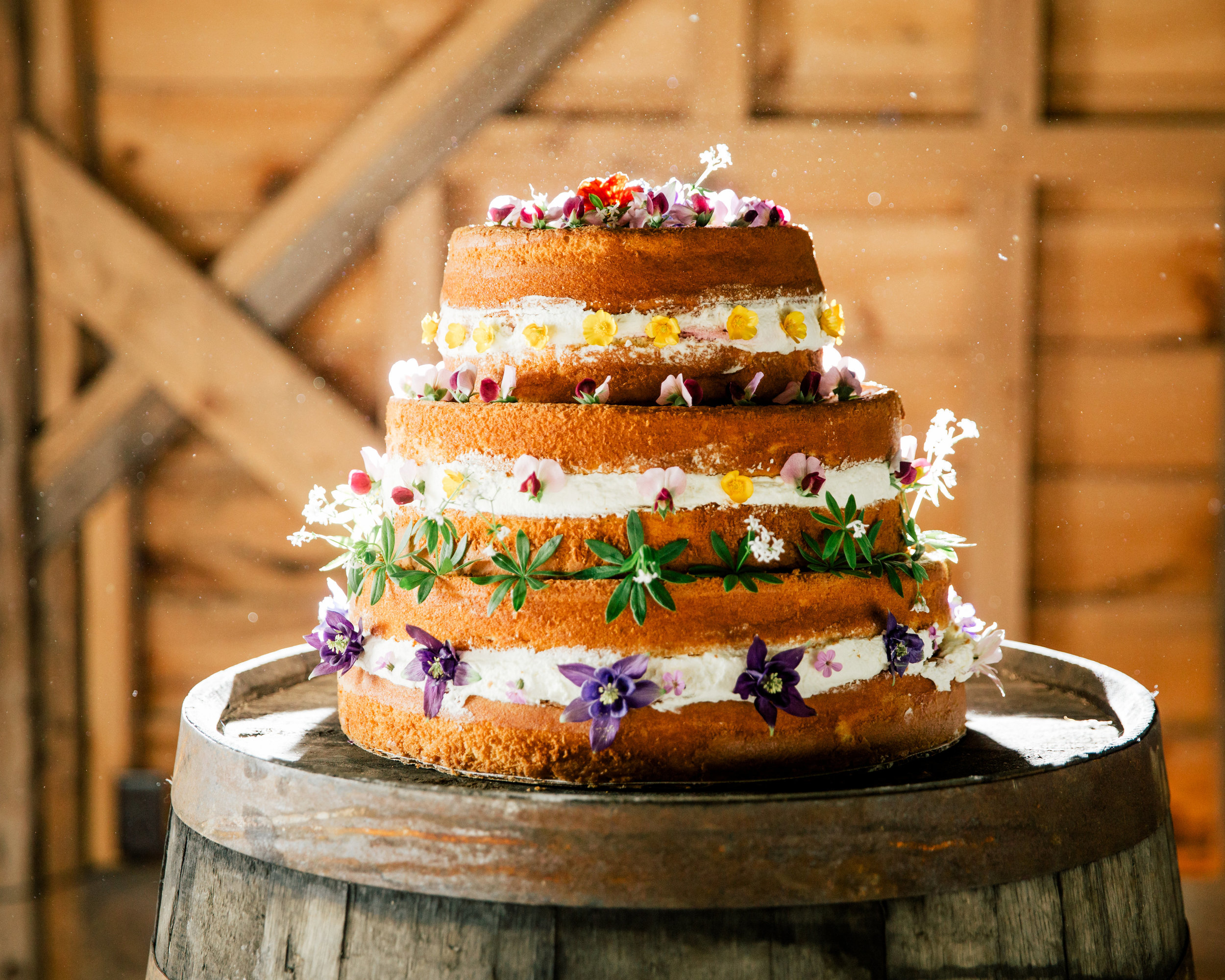 We adorn the cake with edible flowers grown on the farm