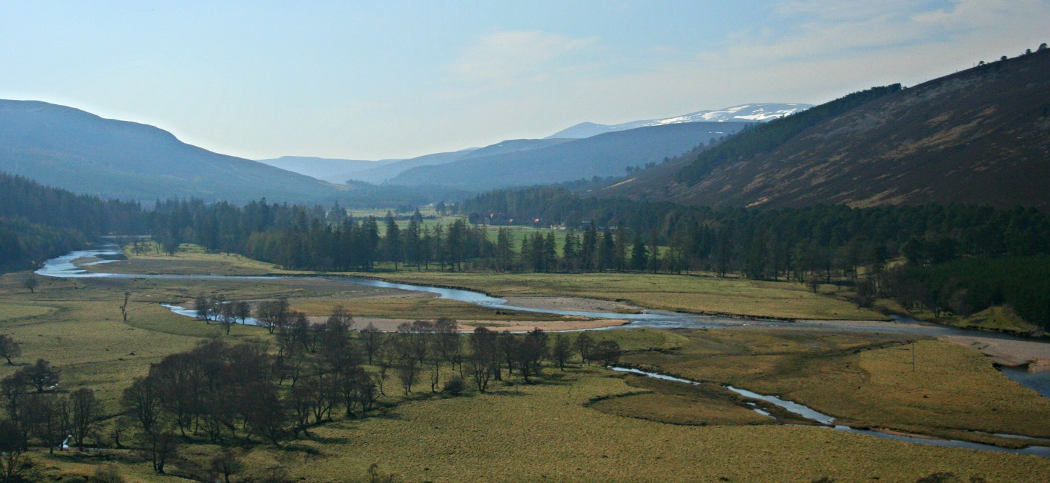 Upper Deeside, west of Braemar, Aberdeenshire. Lots of roadside stopping places to view the young and meandering River Dee. The National Trust for Scotland's Mar Lodge is hidden in the trees in the centre.