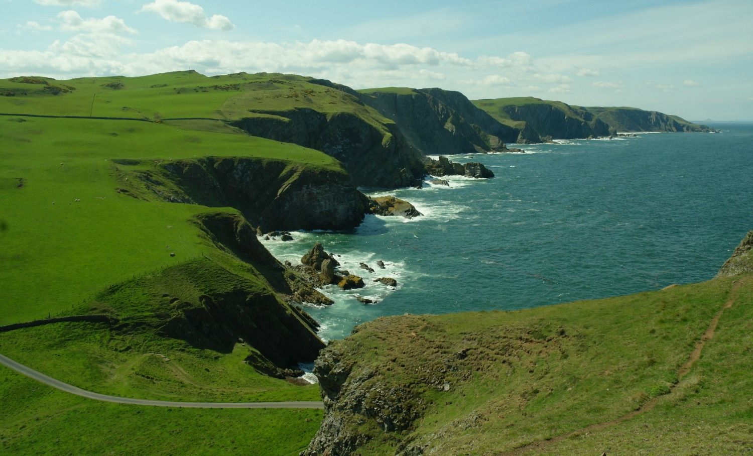 Looking up the coast from St Abb's Head in the Scottish Borders. It's green, green, so green! The lighthouse access road, bottom left, was used for the chase scene where Captain Waggett follows the islanders' whisky-laden lorry.