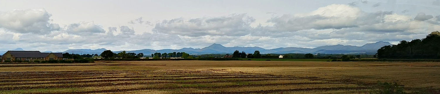 This is a quick snapshot from a moving bus on the M9 just by Stirling, looking west. Ben Ledi is in the centre. Ben Lomond appears above the rooftop, far left. Ben Venue in the Trossachs is also on the left, beyond the tallest tree in that group. The last hill on the right is Stuc a' Chroin - on the far right, with its neighbour Ben Vorlich just obscured y the woods.