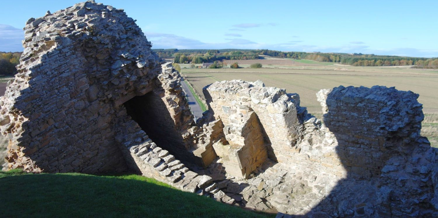 Goodbye, north wall. Here at Duffus Castle the stonework has parted company from the main structure. Still, it's about 700 years old! Note today's approach road, just left of centre.