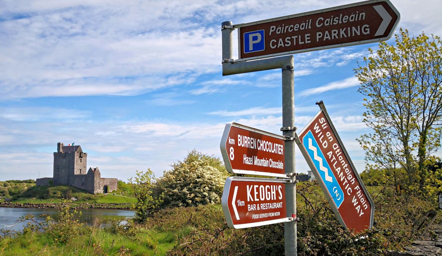 Dunguaire Castle  and a Wild Atlantic Way signpost. The WAW - gosh, how the logo must have written itself. The blue and white sign is hard to miss. Sorry about the way this one points down. It'll be fixed by the time you get here though.