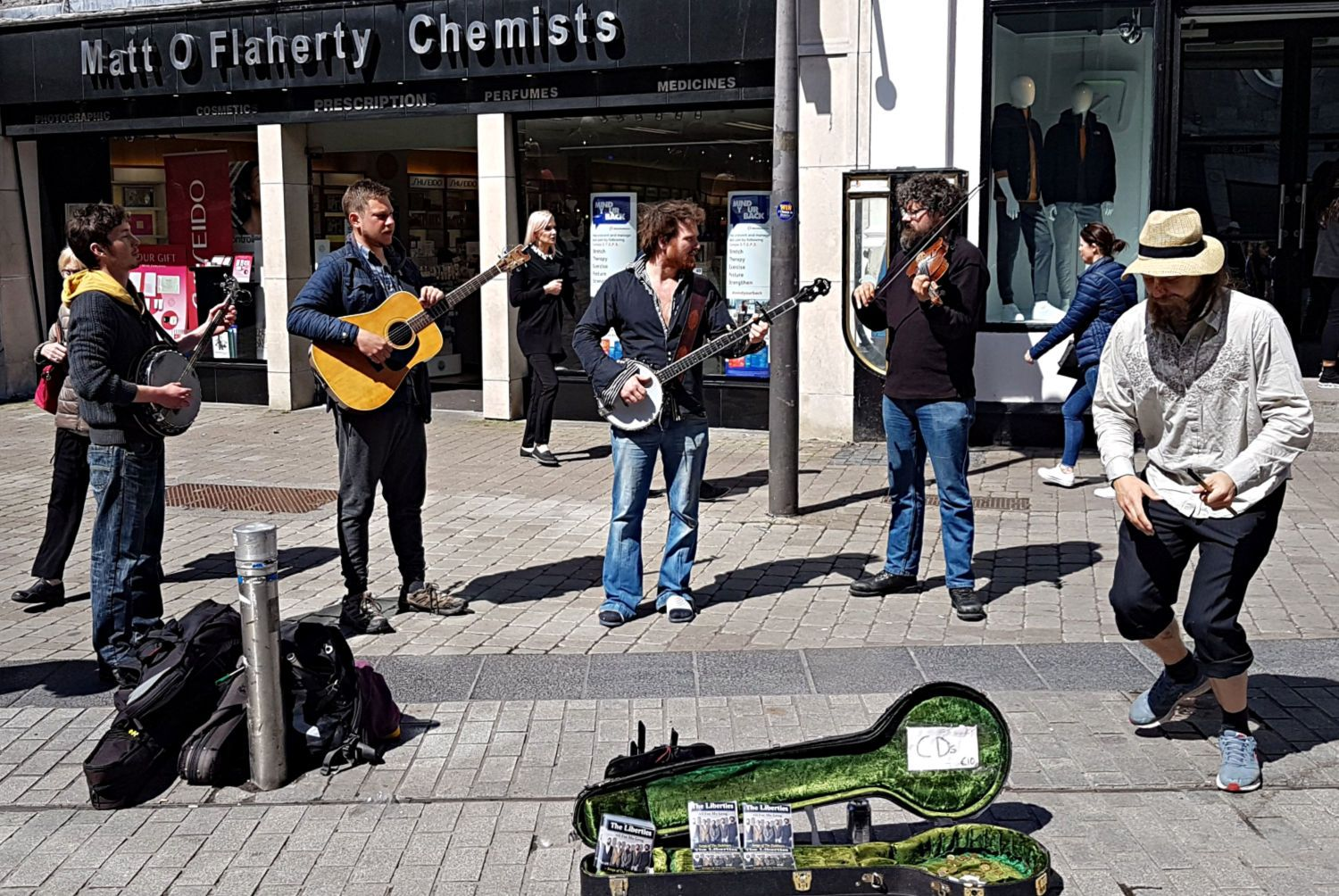 Normally, I'd crop most of the top off a picture like this but I can't resist keeping in the shop name just because I love the way even the chemist shops sound authentically Irish. Oh, wait, this is supposed to be a picture of some street musicians. Note they're selling CDs (The Liberties) and they also do a Dubliners tribute show. Och, well, so they must be OK then…