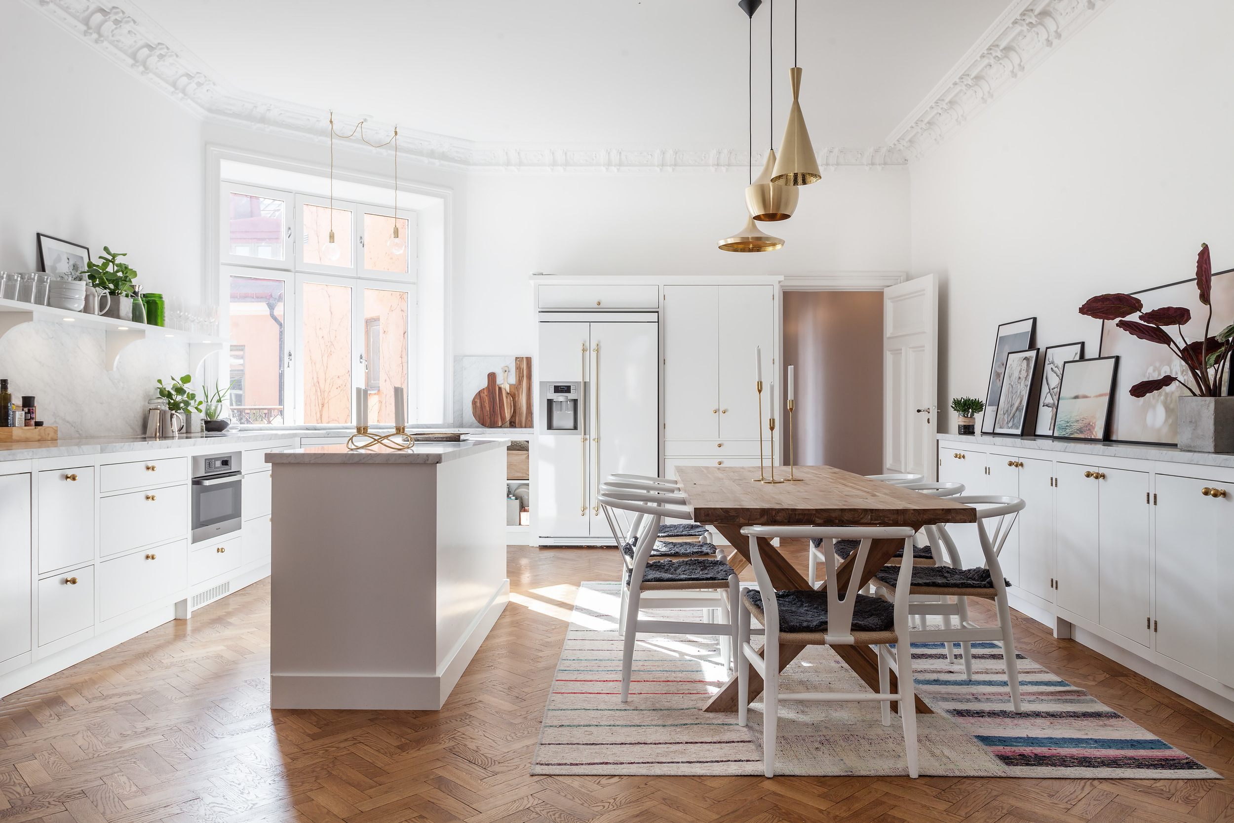 Kitchen with lots of white, marble and brass.
