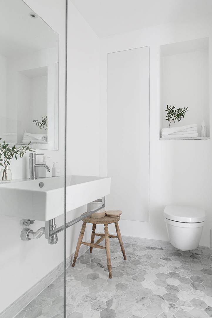 Hexagon marble tiles in a white bathroom.