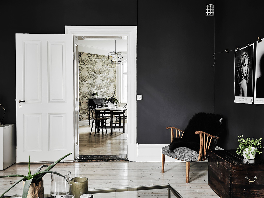Love the view of that leafy wallpaper from this dark and minimalistic room.