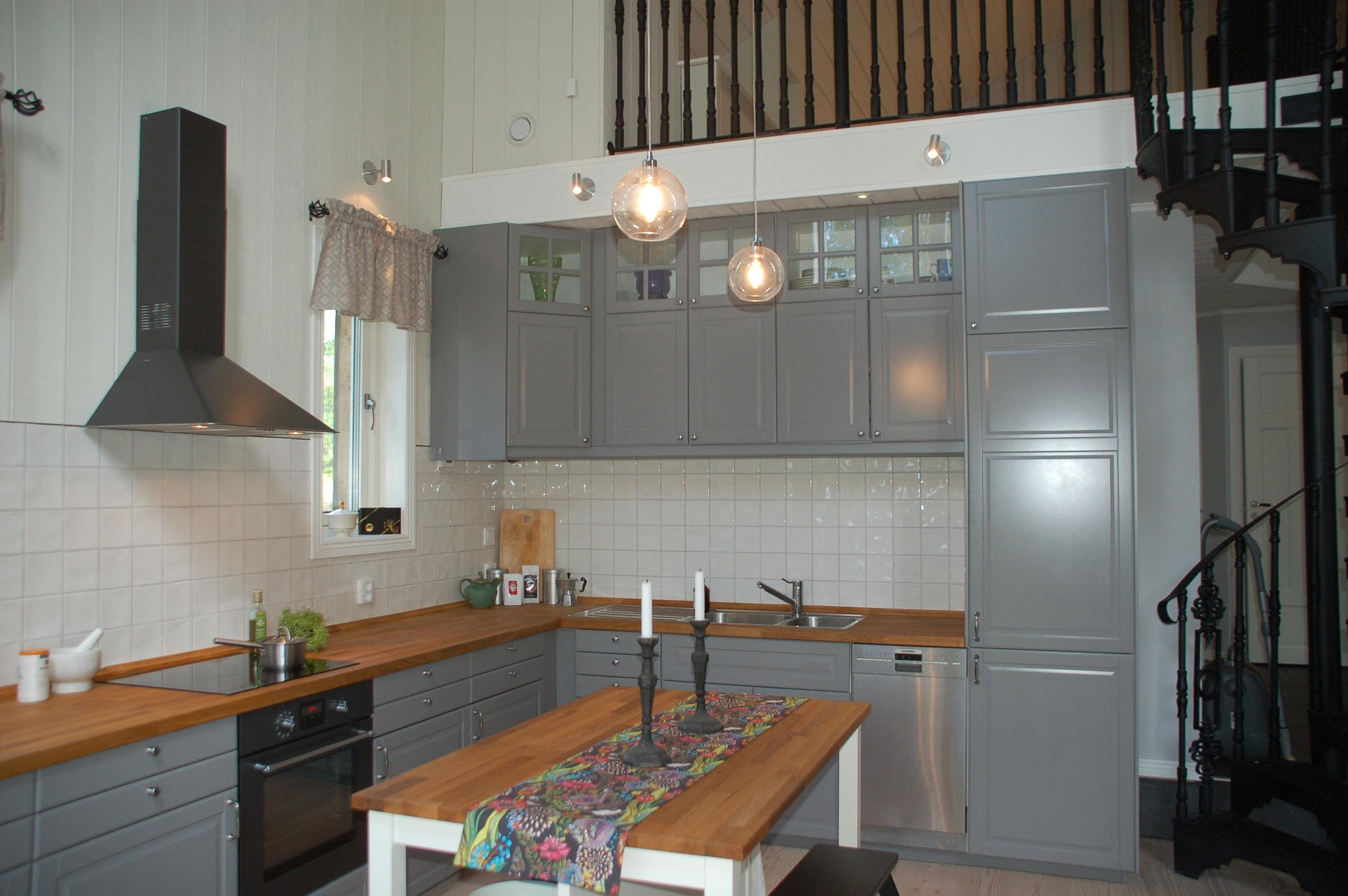 Grey IKEA kitchen with black appliances.
