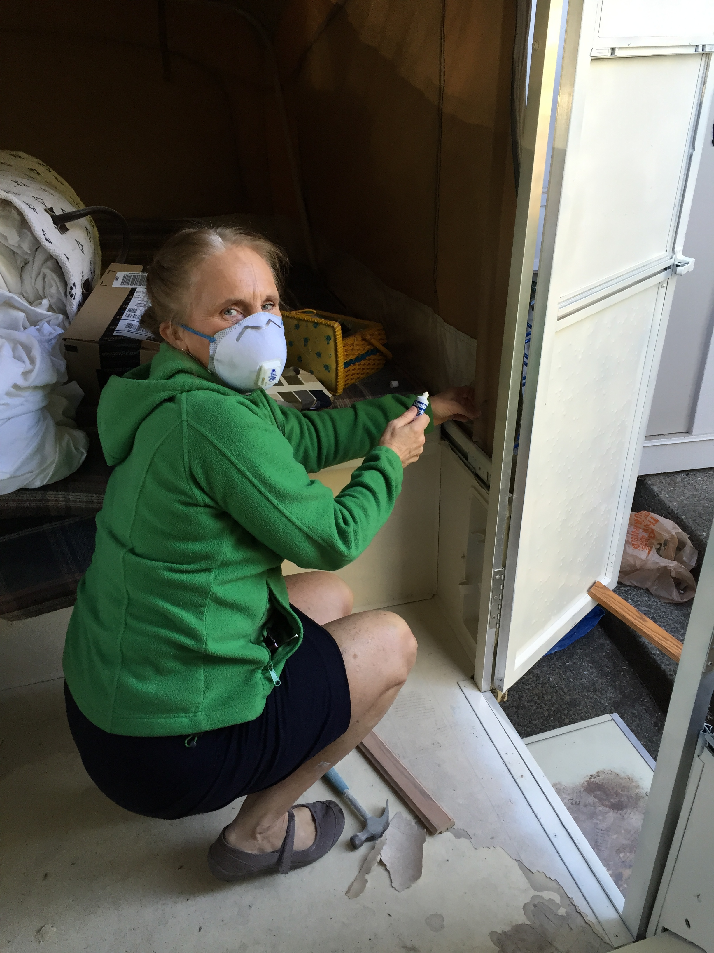 This is my mom, dressed in her church clothes and sewing patches onto the canvas of my tent trailer while I painted the cabinets.