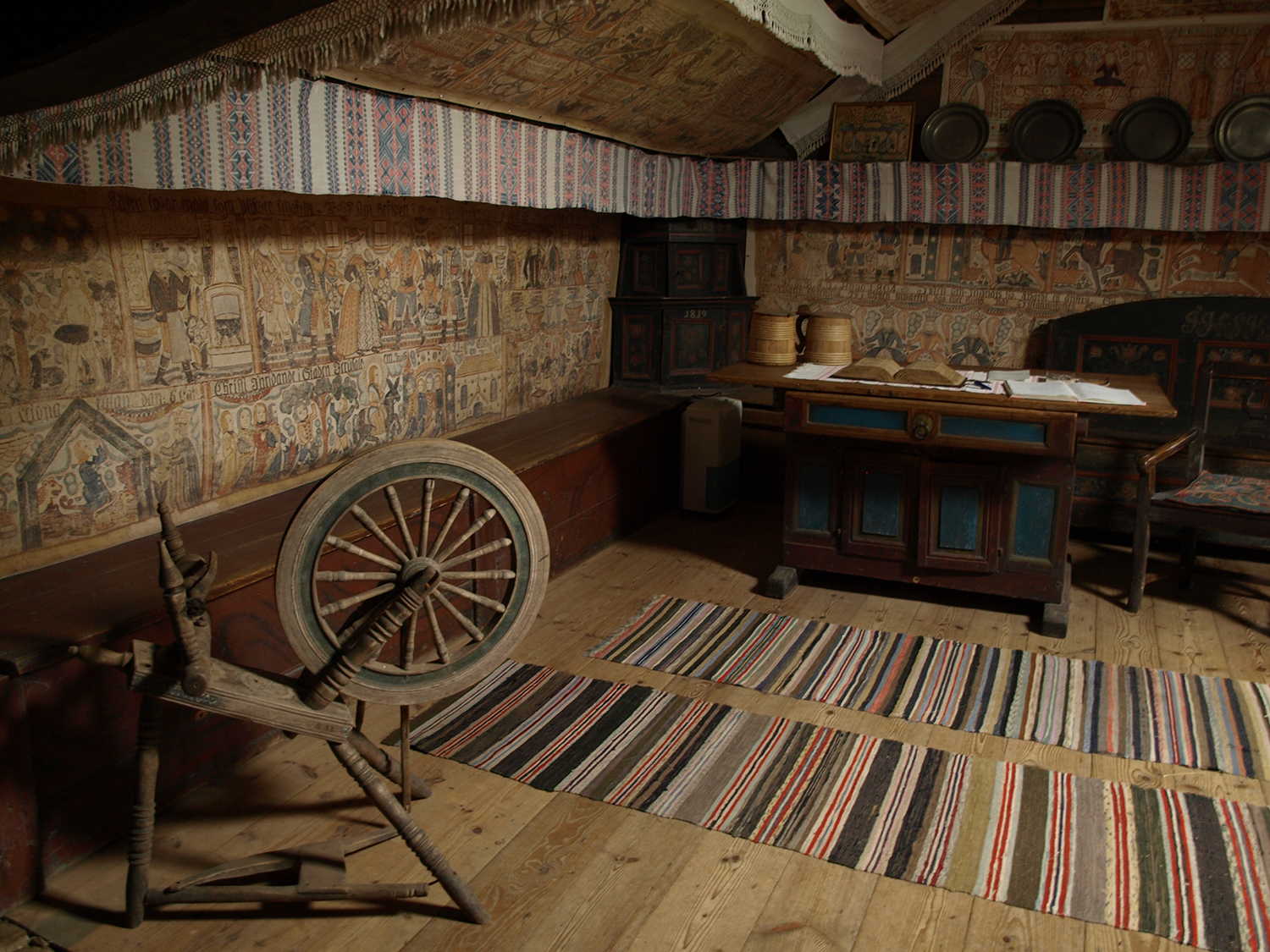 Interior of a ryggåstugga with facsimiles of peasant paintings showing how they would have hung on special occasions.