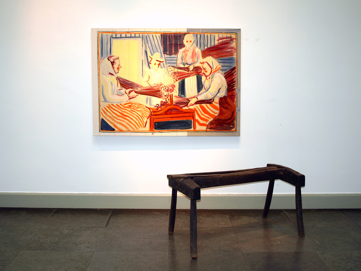 """Installation shot of """"Three Women Working Flax, 2013"""", with a flax breaker from the museum collection."""