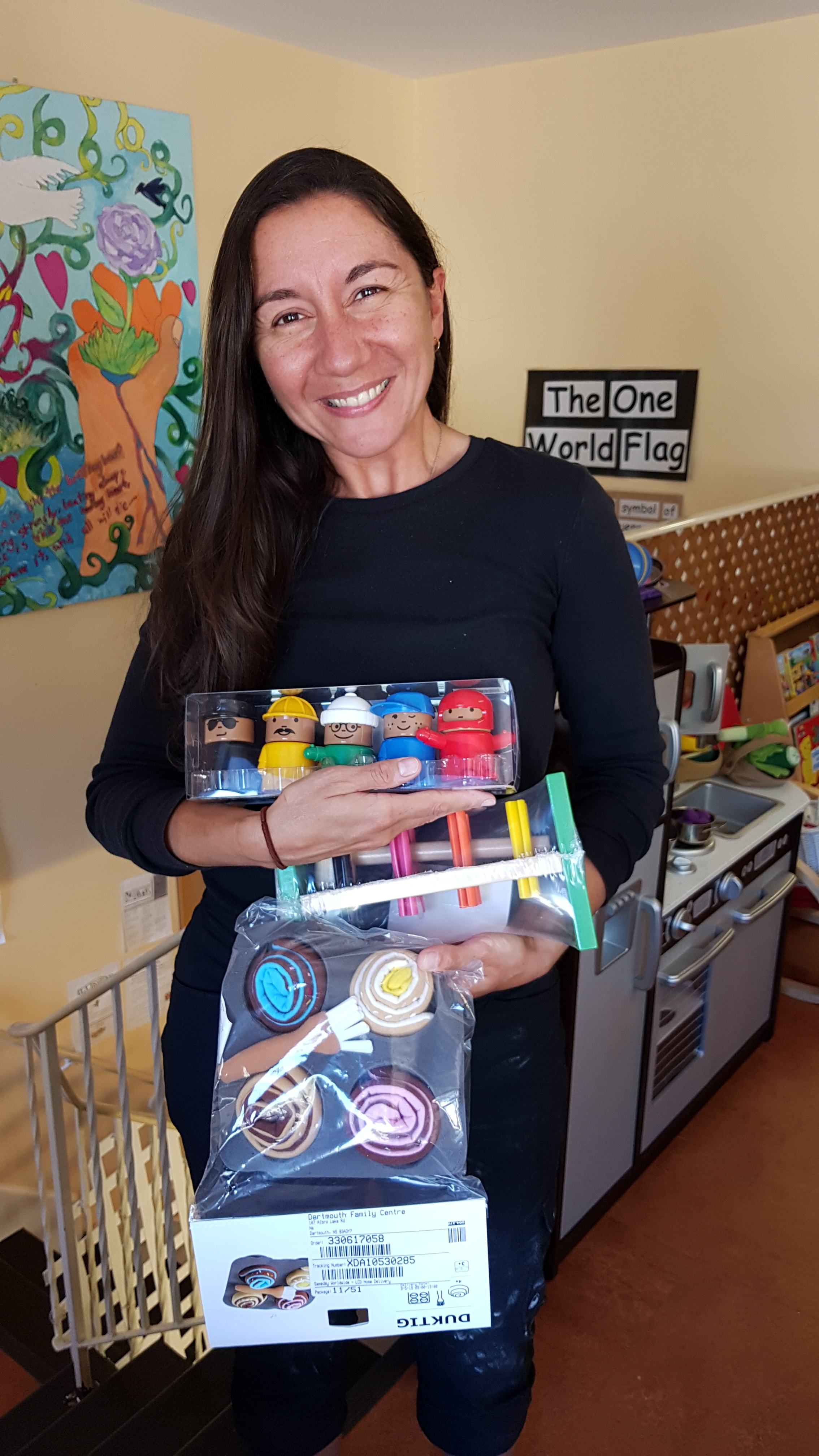 Maria (Early Childhood Educator) holds up some of the new toys that will be used to spark imagination in Child Development.