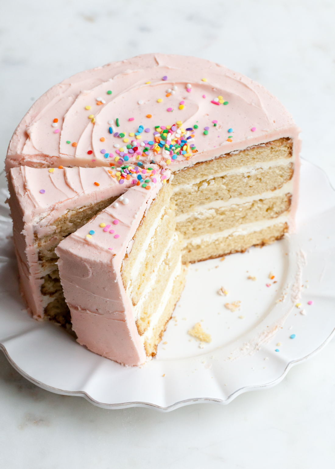 Vanilla bean cake with pink vanilla frosting and sprinkles.