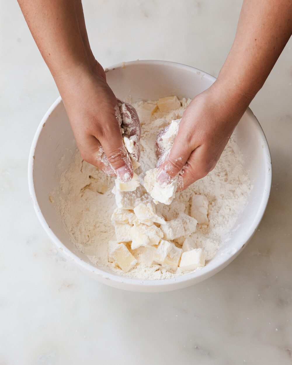 Cut the cold butter into the flour mixture by rubbing pieces between your thumbs and fingers.