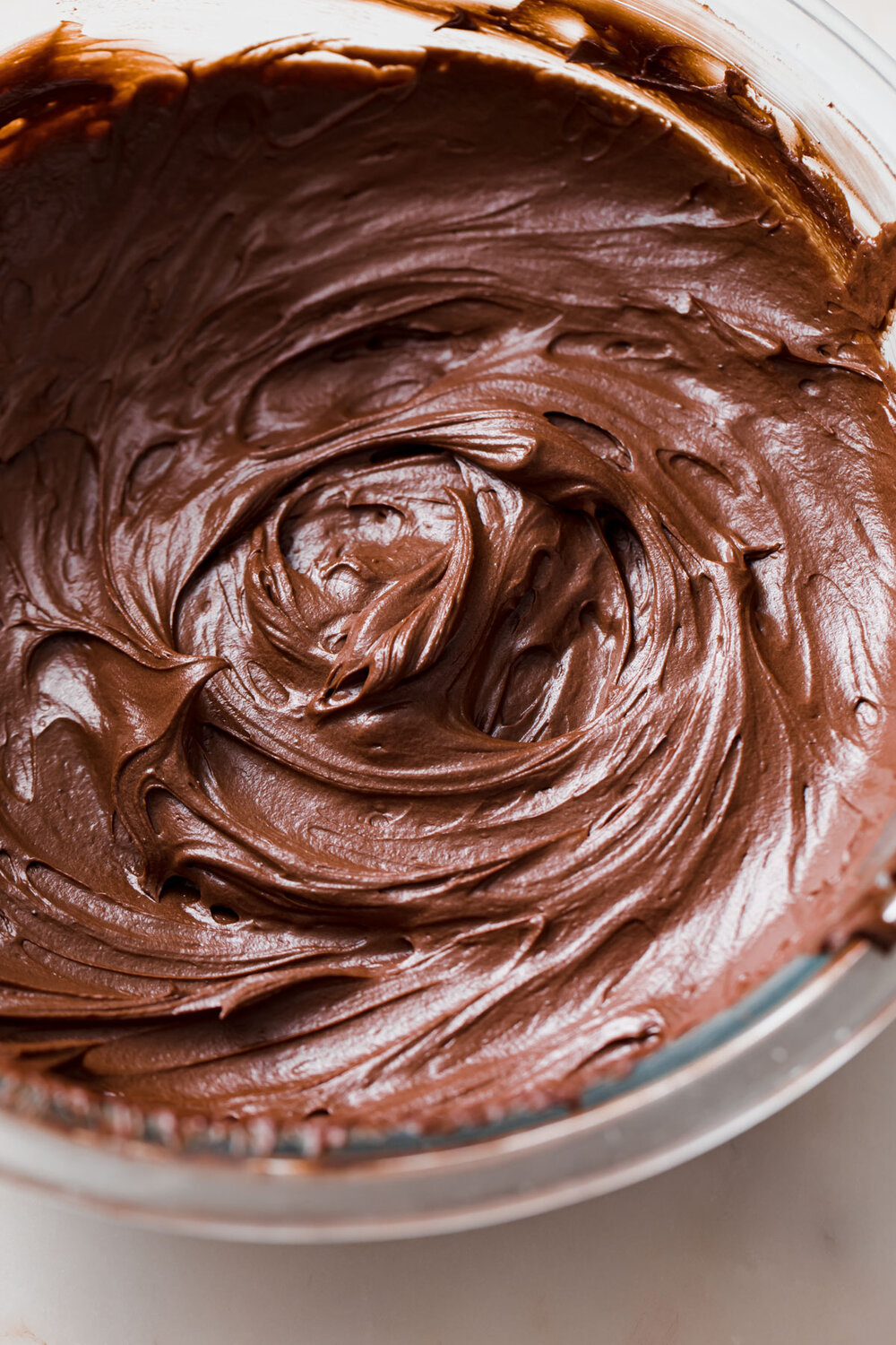 A look inside a bowl of freshly whipped chocolate ganache frosting.