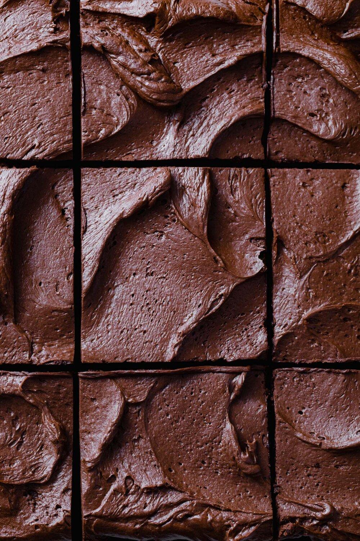 A close-up photo of swirls of whipped chocolate ganache on a sliced chocolate sheet cake