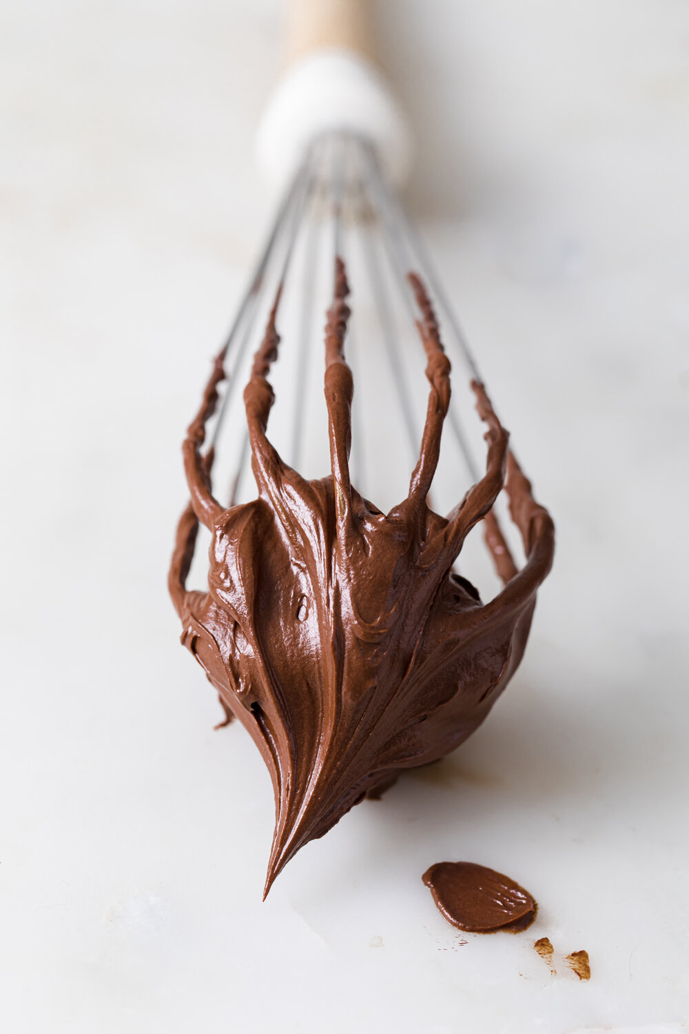 A close-up picture of a whisk covered in soft peaks of whipped chocolate ganache.