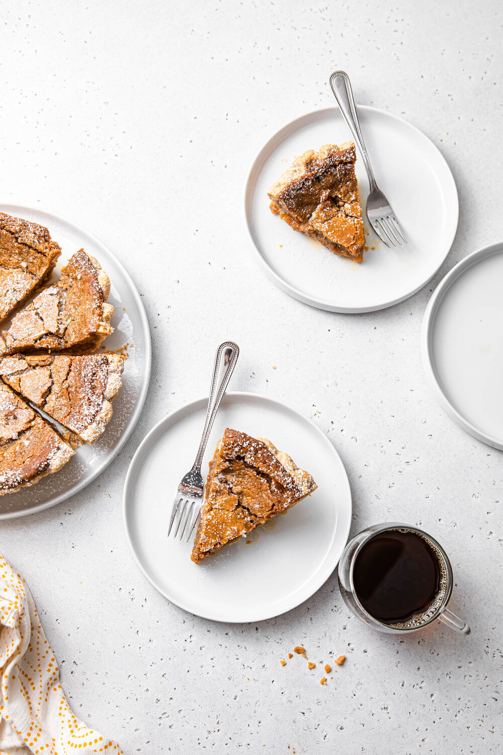 Slices of French Canadian Maple Sugar Pie with powdered sugar on top and a side of coffee.