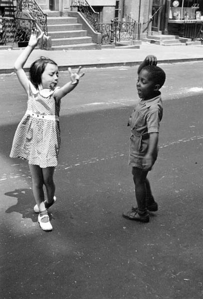 """Hashtag Throwback Thursday. Here I am on the east side of Buffalo, New York with my first girlfriend who lived a block away from me on Roebling avenue. I would walk the block to her house,yell her name, and she would come out. We would hold hands until they got sweaty and then we wouldn't. We would play tag. We would dance. This was before I knew anything about Emmett Till, or Trayvon Martin, o  r Michael Brown, Jr. This was before I knew about war or death. We were just riding bicycles and smiling. I remember once going back to that old neighborhood on a visit. This was when my mother was still alive. Several years ago. We drove slowly to the neighborhood through deep snow on side streets. We were pointing out houses where our old friends had once lived. She pointed out important houses of her past. They leaned into the wind or were boarded up,their paint peeling. We kind of floated through the neighborhood.I am sure that each of us were remembering lazy summer evenings. The adults sitting on lawn chairs in yards, drinking beer, and playing euchre while their children ran along perfectly clipped lawns shouting. She said, """"that empty corner lot there used to be a clam stand. Your father and I used to go on dates there."""" Where the clam stand once stood had become an abandoned lot. The lot in the snow became a white square with several scrub trees poking up out of it, but it was beautiful. We drove past the library and the decomissioned church to the main road, which had been plowed. We stopped at the intersection and paused, taking in the scene. The snow and the gloaming had obscured the decay of this forgotten part of the city. It looked like it did when I was young. It looked like it did when everything was easy and carefree and the only problems children had to deal with were the streetlights coming on and taking baths."""