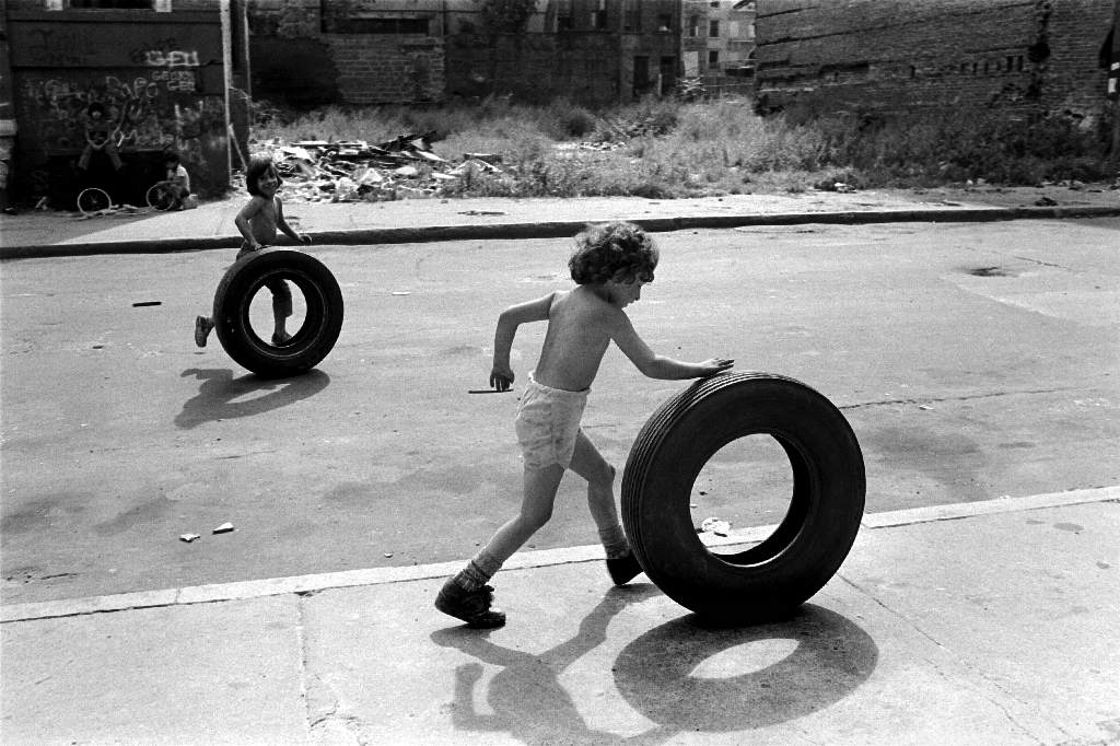 Hashtag Throwback Thursday. Here is a photograph of me in the golden moments of my youth on the east side of Buffalo, New York. I am rolling a tire I found in a vacant lot because my brothers had set fire to my Big Wheel on the railroad tracks by my grandmother's house off of Olympic Avenue. The burning of my Big Wheel had occurred several weeks prior to this photograph being taken. The matches which set fire to the gasoline that had been poured on my Big Wheel had been stolen by my brother from my Aunt Laura who smoked non-filtered Lucky Strikes. My brother will remain nameless, because I swore to him at the time of the theft that I would never tell, otherwise I would receive a fat lip administered by a knuckle sandwich. I did not know what the matches were to be used for at the time I had agreed to the pact. I am eight, still wearing the milk fat of my baby years, and wearing my favorite socks. I am shirtless because I loathed the feel of the hand-me down polyesther shirts of my brothers. I am trying to impress my first girlfriend who lived on Roebling Avenue and wore Jordache jeans. Her eyes shined like smooth wet stones and I longed to hold her hand, but her hand was held by another, and so I rolled my tire like an innocent Sisyphus. Up and down and back again. Over and over. This is what I like to remember. Not that my Big Wheel was melted on the railroad tracks by my brothers who enjoyed burning things and kissing girls behind the garage. Not the smooth wet stones that were the eyes of the girl who lived down the block and would eventually become my first girlfriend. Not the Lucky Strikes of my aunt who is a photograph now. Not my grandmother, that hero of a woman who made the love that was my mother, both of whom who are no longer. No. I like to remember the overwhelming joy and beauty of those moments. The truth and simplicity. A tire lay in a vacant lot and I rolled it. I was glad to be in the world with the air rushing over my slick summer body, full on my mother's potato pancakes. Intimate with everything I wanted. Laughing with my friend. The dream quietly waiting for the taking. The smooth wet stones still somehow shone on me. The way it was and the way it could be all wrapped up together neatly in a circle that I rolled and let go and watched as it went on and on - down the street, and then further and still somehow continues on.