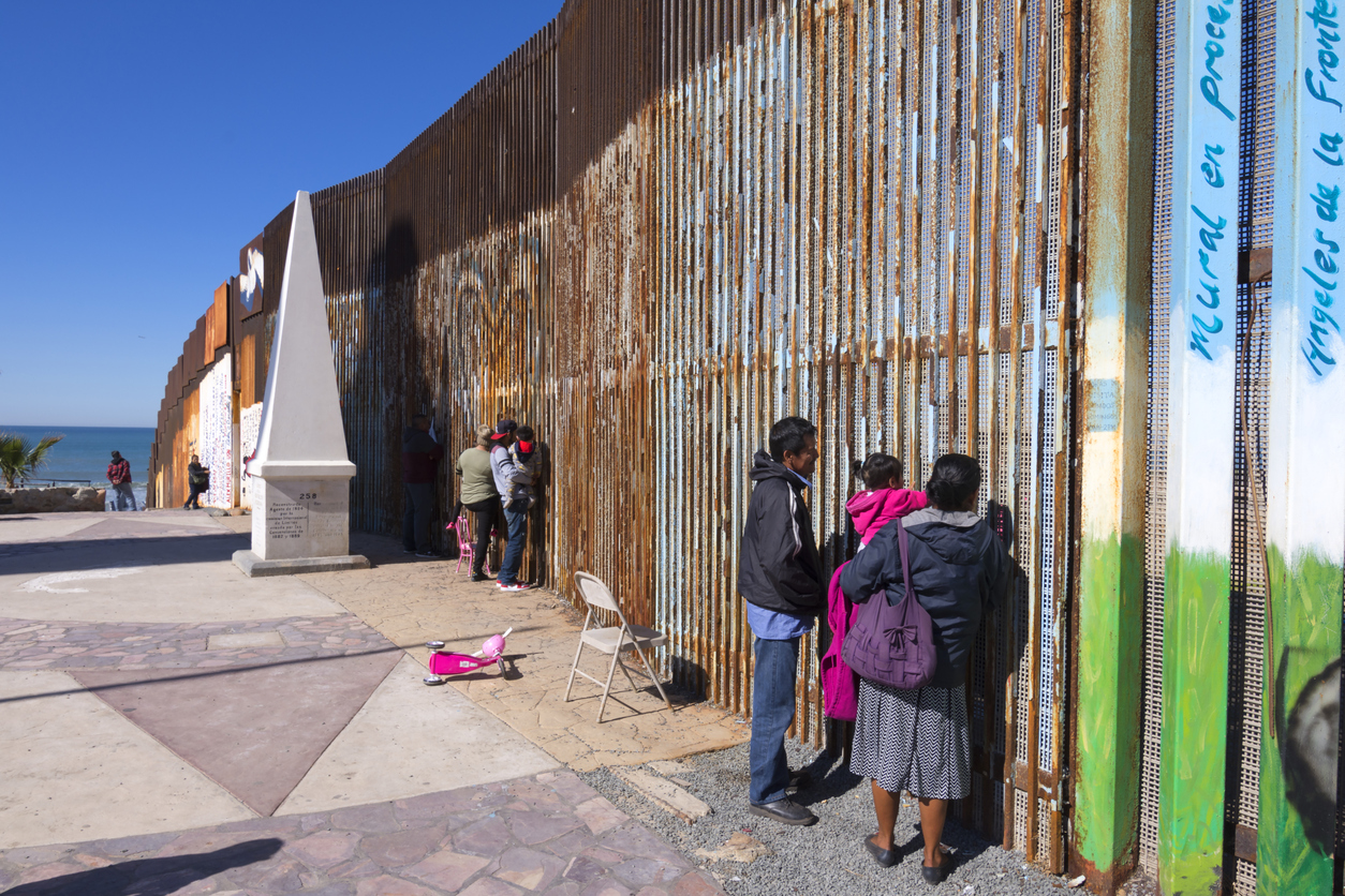 Playas de Tijuana, Mexico - January 28, 2017: Mexican families living in Tijuana visit with family members living in the United States by meeting at the border wall in Playas de Tijuana. Photo: Shakzu