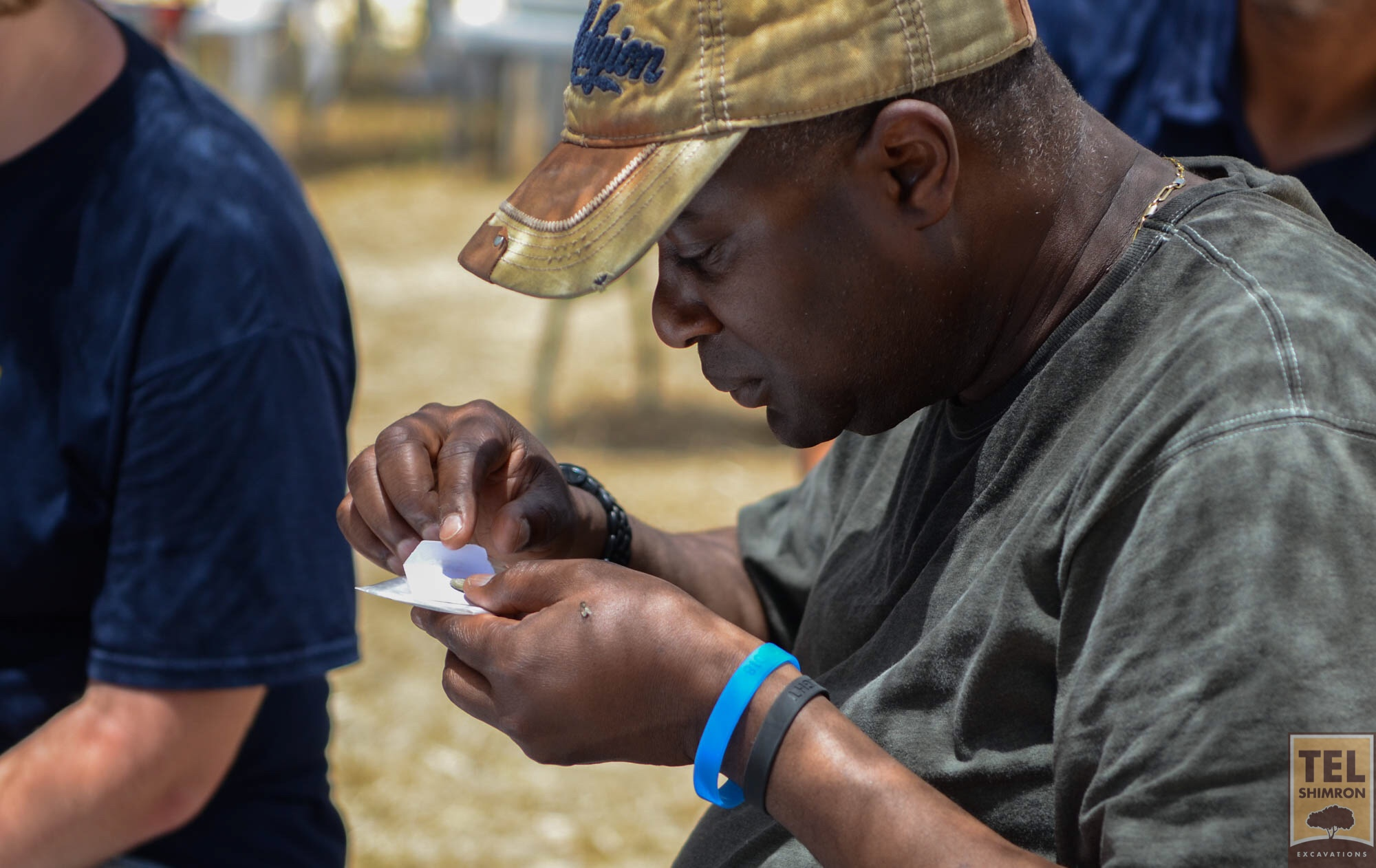 Examining a coin found during excavation