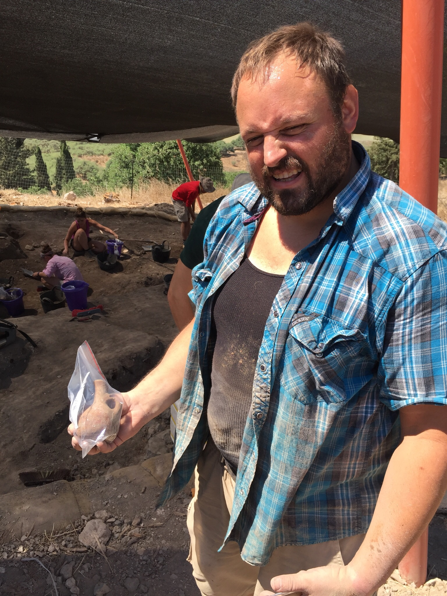 Grid Supervisor Josh Walton holding a small juglet found in Grid 33