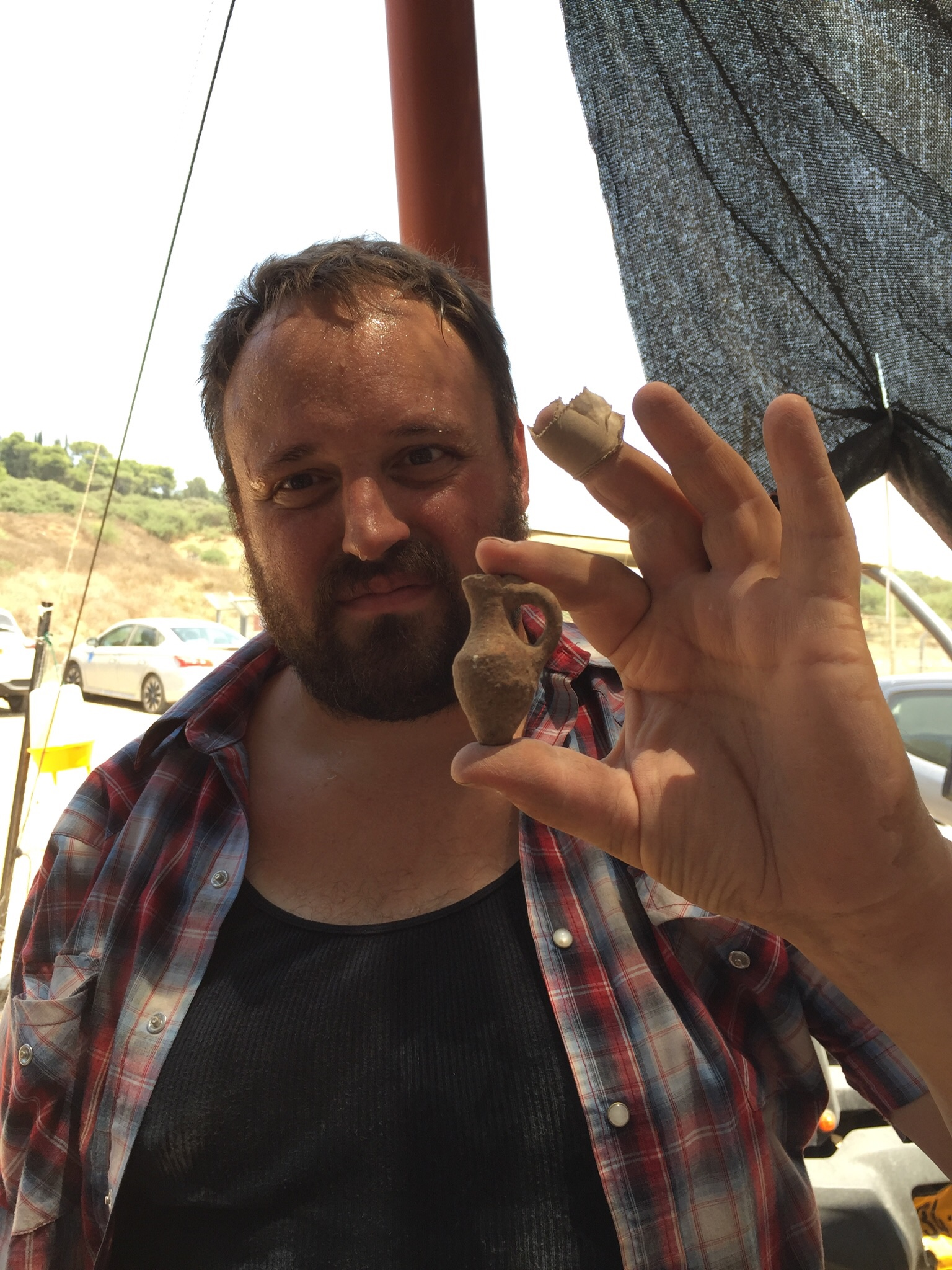Grid Supervisor Josh Walton holding a small juglet he found while excavating today