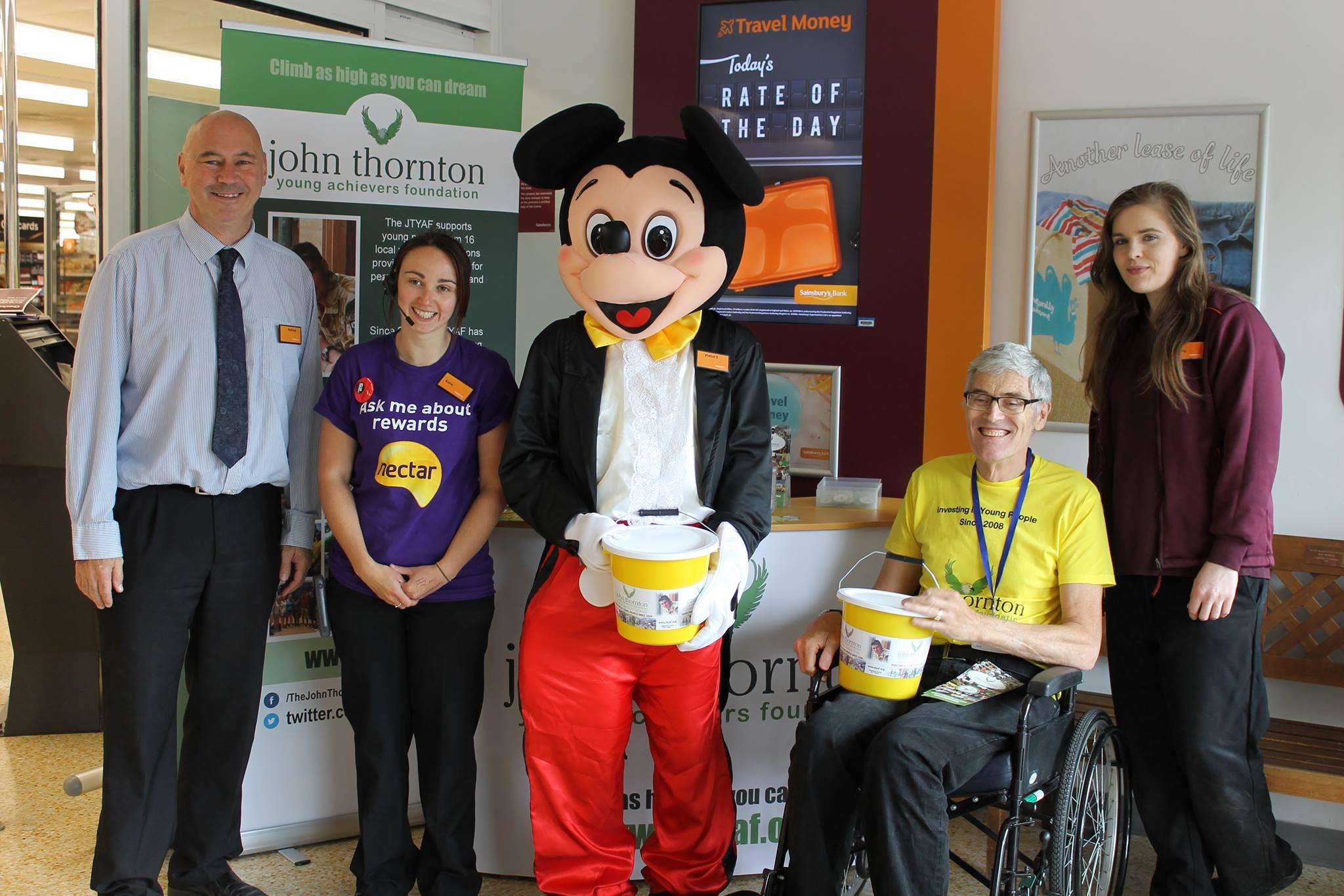 Sainsbury's manager Richard Lockett, a sainsbury's volunteer, mickey mouse, volunteer David Howelett and another sainsbury's volunteer